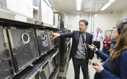 Researcher, Kawaoka points to a metal and glass holding tank as hands holding microphones are seen
