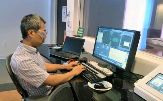 GE Researcher seated at a computer