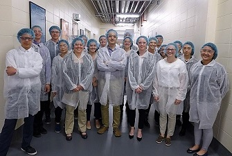Students wearing white labcoats and blue hairnets and safety goggles photograpfhed in a long hallway