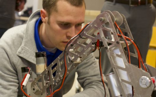 man is featured looking closely at a robotic arm of a rover device