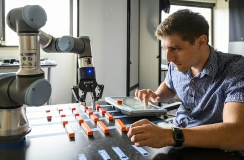 Man in lab with laptop, and robotic arm