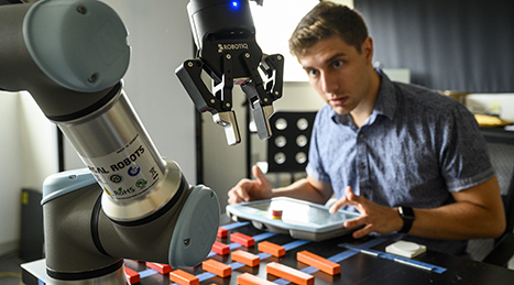 Man working in a robotics lab: robot arm in foreground, man in background slightly out of focus