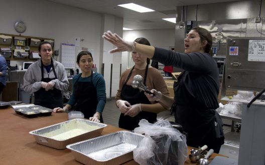 Group stands around food containers and listens to a woman speak. Featured in an industrial kitchen