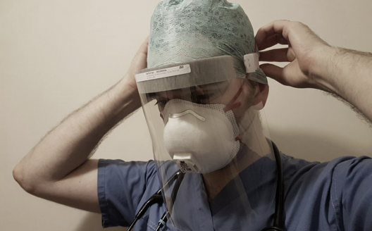 Health care worker wears face shield