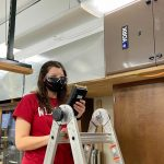 Masters student Stephanie Richards measures air quality near a test furnace