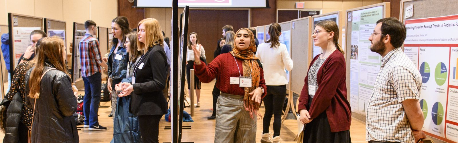 Hibah Hafeez (right) talks about her research project and poster display during the Undergraduate Symposium in Varsity Hall inside of Union South at the University of Wisconsin-Madison